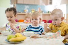 Kids eating in kindergarten or day care centre royalty free stock images