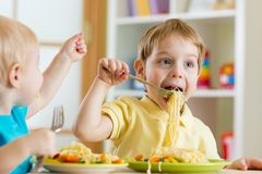 Kids eating in kindergarten. Kids eating food in nursery or at home Stock Image