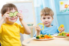Kids eating in kindergarten. Kids eating healthy food in kindergarten or at home Royalty Free Stock Photo