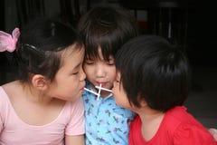 Kids eating lollipop. Kids sitting together on the floor & enjoying lollipop royalty free stock image