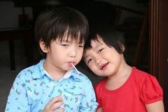 Kids eating lollipop. Kids sitting together on the floor & enjoying lollipop stock photography