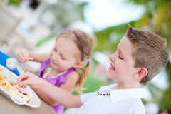 Kids eating lunch. Boy and girl eating lunch at outdoor restaurant royalty free stock photography
