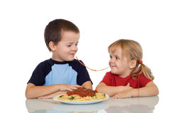 Kids eating pasta. Two kids eating the same string of pasta - isolated Royalty Free Stock Images