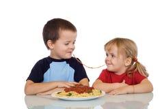 Kids eating pasta royalty free stock images