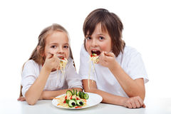 Kids eating a pasta dish. Kids eating a spaghetti dish with big appetite - isolated Royalty Free Stock Photos