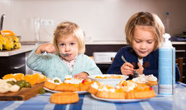 Kids eating pastry indoors Stock Photography