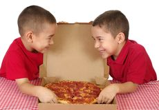 Kids eating pizza. Six and seven year old boys eating a take-out pizza, on white background Royalty Free Stock Images