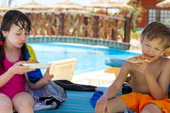 Kids eating pizza. A pair of kids eating pizza by the pool stock photos