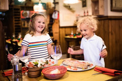 Kids eating pizza in Italian restaurant. Kids eat pizza, pasta and salad in traditional restaurant. Eating out with children. Boy and girl having dinner in stock photography