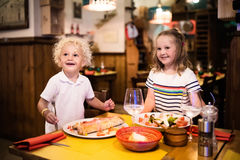Kids eating pizza in Italian restaurant. Kids eat pizza, pasta and salad in traditional restaurant. Eating out with children. Boy and girl having dinner in royalty free stock photo