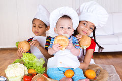 Kids eating sandwiches. Three kids in white aprons and hats eating sandwiches Stock Photos