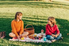 Kids eating snacks outside, family picnic. Kids eating snacks outside. Children resting in the park on a nice sunny day sitting on the blanket Stock Images