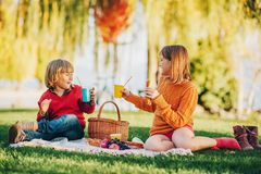 Kids eating snacks outside, family picnic. Kids eating snacks outside. Children resting in the park on a nice sunny day sitting on the blanket Royalty Free Stock Images