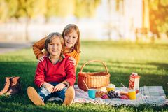 Kids eating snacks outside, family picnic. Kids eating snacks outside. Children resting in the park on a nice sunny day sitting on the blanket Royalty Free Stock Photo