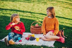 Kids eating snacks outside, family picnic. Kids eating snacks outside. Children resting in the park on a nice sunny day sitting on the blanket Stock Photos