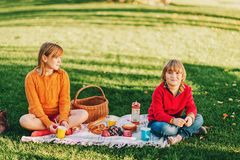 Kids eating snacks outside, family picnic. Kids eating snacks outside. Children resting in the park on a nice sunny day, sitting on the blanket Royalty Free Stock Photo