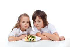 Kids eating spaghetti. Kids eating a decorated spaghetti dish - isolated Stock Photos