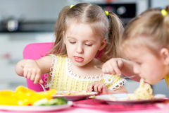 Kids eating spaghetti with vegetables in nursery Stock Images
