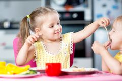 Kids eating spaghetti with vegetables in nursery Stock Photography