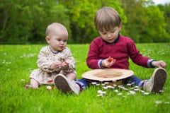 Kids eating strawberries. Cute kids sharing strawberries sitting in the grass Stock Image