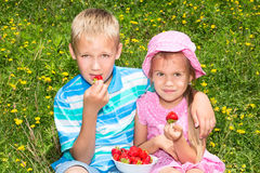 Kids eating strawberries Royalty Free Stock Image