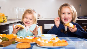 Kids eating tasty pastry indoors Royalty Free Stock Image