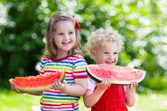 Kids eating watermelon in the garden. Child eating watermelon in the garden. Kids eat fruit outdoors. Healthy snack for children. Little girl and boy playing in Royalty Free Stock Photo