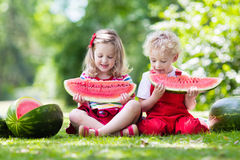 Kids eating watermelon in the garden Royalty Free Stock Image