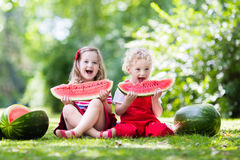 Kids eating watermelon in the garden. Child eating watermelon in the garden. Kids eat fruit outdoors. Healthy snack for children. Little girl and boy playing in royalty free stock photos
