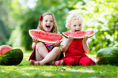 Kids eating watermelon in the garden. Child eating watermelon in the garden. Kids eat fruit outdoors. Healthy snack for children. Little girl and boy playing in Royalty Free Stock Image