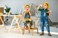 Kids eating in workshop. Two little boys in hard hats and denim overalls eating sandwiches and drinking coffee in workshop Royalty Free Stock Photography