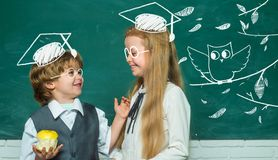 Kids education. Girl and boy with happy face expression near desk with school supplies. School kids. stock photos