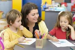 Kids and Educator Playing at Kindergarten. Kids drawing at kindergarten being supervised by educator Royalty Free Stock Photo