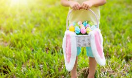 Kids with eggs basket on Easter egg hunt. Kids with eggs basket and bunny ears on Easter egg hunt in sunny spring garden. Little boy searching for colorful candy royalty free stock images