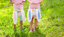 Kids with eggs basket on Easter egg hunt. Kids with eggs basket and bunny ears on Easter egg hunt in sunny spring garden. Little boy and girl searching for stock image