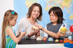 Kids in elementary science class study our solar system- focus o. Kids and teacher in science class study the solar system - examining the planets from a scale stock image