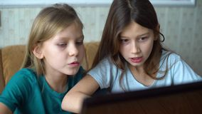 Kids emotions during playing computer games. Little girls sitting in front of laptop monitor. online surfing, internet and technologies stock video