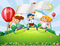 Kids with an empty banner running at the hilltop with a rainbow Royalty Free Stock Images