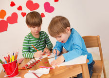 Kids engaged in Valentine's Day Crafts: Love and Hearts. Kids, children, doing Valentine's day arts and crafts with hearts, pencils, paper, love concept stock image