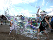 Kids enjoy bubble chase Royalty Free Stock Images