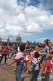 Kids enjoy bubble chase Stock Photos