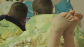 Kids enjoy online at night. Happy children looking at the tablet. boys have fun on-line stock footage