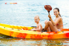 Kids enjoying paddling in kayak on the sea water Royalty Free Stock Images
