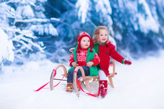 Kids enjoying sleigh ride on Christmas day. Little girl and baby boy enjoying a sleigh ride. Child sledding. Toddler kid riding a sledge. Children play outdoors Royalty Free Stock Images