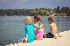 Kids enjoying summer vacation at the lake. Three kids sitting on the dock of the lake enjoying their summer vacation together. View from behind Stock Photography