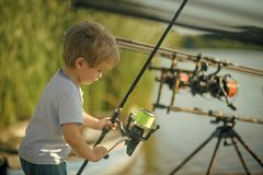 Kids enyoj happy day. Fishing, angling, activity, adventure, sport. Little boy learn to catch fish in lake or river. Summer vacation, hobby, lifestyle Royalty Free Stock Photo