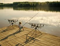 Kids enyoj happy day. Fishing fish concept. Fishing boy with rod, reel on wooden pier at freshwater Stock Photography