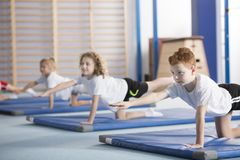 Kids exercising balancing yoga pose. Primary school boy and other kids exercising a balancing table yoga pose during extracurricular gym class to help with Stock Image