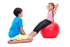Kids exercising together - using a large rubber gymnastic ball Royalty Free Stock Photo