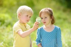 Kids exploring nature with magnifying glass. Close up. Little boy and girl looking with magnifying glass. Summer activity for inquisitive child royalty free stock image